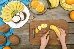 geernteter Schuss der Person reife Banane auf hölzernem schneiden stockfotografie