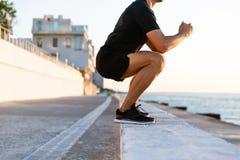 geernteter Schuss der Sportlerstellung hockt auf Geländer stockfotos