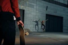 geernteter Schuss des Mannes stehend mit Skateboard während sein Partner, der Trick tut lizenzfreies stockfoto