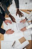 geernteter Schuss des Teams der Architekten, die zusammen mit Vertrag arbeiten lizenzfreie stockfotos