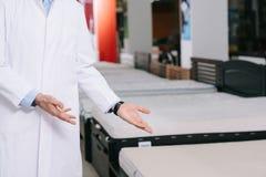 geernteter Schuss des Verkäufers zeigend auf orthitic Matratzen im weißen Mantel lizenzfreie stockfotos