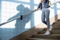 geernteter Schuss des weiblichen Reisenden mit dem Rucksack, der die Treppe hinunter geht stockfotografie