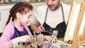 Geernteter Schuss einer netten lächelnden Unterhaltung des kleinen Mädchens mit ihren mischenden Farben des Vatis am Kunstunterri stockfotos