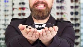 Geernteter Schuss eines bärtigen Mannes, der Gläser zur Kamera heraus halten lächelt stock footage