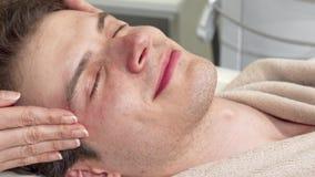 Geernteter Schuss eines glücklichen Mannes, der Kopf- und Gesichtsmassage in der Badekurortmitte genießt stock video footage