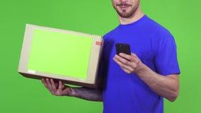Geernteter Schuss eines Lieferboteen mit einem Paket, das seinen Kunden verwendet intelligentes Telefon simst stock footage