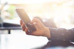 Geernteter Schuss von Frau ` s übergibt das Halten des Handys, der online kaufen macht Optische Effekte Frau, die Handy beim Sitz Stockbilder