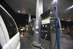 Geerntetes Auto mit Ansicht von Tanksäulen und von Erdgas Lizenzfreie Stockbilder