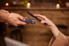 Geerntetes Bild der Frau zahlend mit der Handyzahlung technolgy in einer Kaffeestube lizenzfreie stockfotos