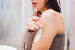 Geerntetes Bild der schönen jungen Frau im Badtuch, das Körperlotion auf ihren Schultern und Stellung im Badezimmer anwendet Bade Lizenzfreie Stockfotos