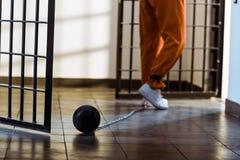 geerntetes Bild des Gefangenen gehend in orange Uniform mit dem Gewicht begrenzt stockfotos