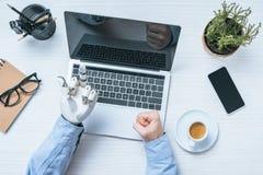 geerntetes Bild des Geschäftsmannes mit dem Armprothesevertretungsmittelfinger zum Laptopschirm bei Tisch stockfotografie