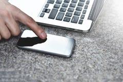 Geerntetes Bild des Geschäftsmannes mit Laptop an der Straße, die dem Mitarbeiter Textnachrichten schickt stockbild