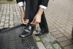 Geerntetes Bild des Geschäftsmannes seinen Schuh auf Bank binden lizenzfreies stockfoto