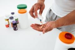 Geerntetes Bild des jungen Sportlers Vitamine und Sportpillen halten stockbild
