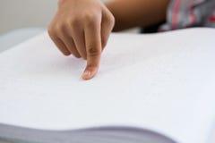 Geerntetes Bild des Kindes Blindenschrift-Buch lesend Stockbild
