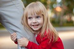 Geerntetes Bild des netten kleinen Mädchens, das Kamera beim Umarmen des Beines ihres Vaters lässt ihn nicht gehen betrachtet Lizenzfreie Stockfotografie