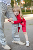 Geerntetes Bild des netten kleinen Mädchens, das Kamera beim Umarmen des Beines ihres Vaters lässt ihn nicht gehen betrachtet Stockfoto