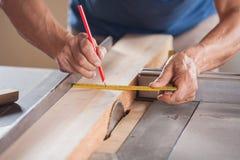 Geerntetes Bild des Tischlers Measuring Wood At Stockbild
