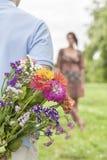 Geerntetes Bild des versteckenden Blumenstraußes des Mannes von der Frau im Park Stockbild