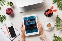 geerntetes Bild des weiblichen Freiberuflers digitale Tablette mit Anmeldung auf Schirm mit den Geräten und Kaffee bei Tisch halt stockbilder