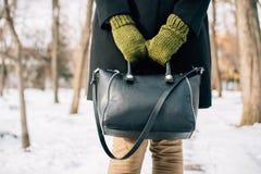 Geerntetes Bild einer Frau in einem Mantel, der ihren Geldbeutel hält stockfotos