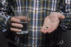 Geerntetes Bild einer kranken Person, die eine Tablette und ein Glas Wasser, auf einem grauen Hintergrund, Hände eines Arbeiters  lizenzfreie stockfotos