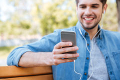 Geerntetes Bild eines jungen Mannes, der mit Handy sitzt stockfotografie