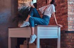 Geerntetes Bild eines kühlen modernen Mädchens, das eine weiße Spitze und Jeans sitzen auf einer Tabelle mit einer Schale Mitnehm Stockfotos