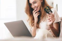 Geerntetes Bild von Dame, welche die Laptop-Computer hält Kreditkarte verwendet stockfotos