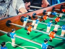 Geerntetes Bild von den aktiven Leuten, die foosball spielen Tabellenfußball plaers Tischfußball des Freundspiels zusammen lizenzfreies stockbild