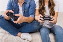 geerntetes Bild von den Paaren, die Videospiel durch Steuerknüppel auf Sofa spielen stockbild