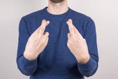 Geerntetes Nahaufnahmefotoportr?t der ungewissen unconfident Kerlherstellung kreuzte Finger lokalisierten grauen Hintergrund stockfotografie