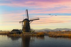 Free Geese Flying Over Sunrise On The Frozen Windmills Alignment Royalty Free Stock Image - 181793506