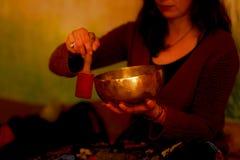 Geestelijk die meisje in meditatieve geluiden van tibetian kom wordt ondergedompeld stock foto's