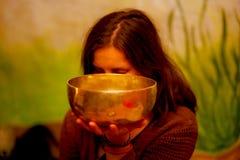 Geestelijk die meisje in meditatieve geluiden van tibetian kom wordt ondergedompeld stock fotografie