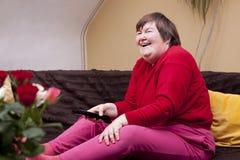Geestelijk - de gehandicapte vrouw het letten op televisie en geniet van royalty-vrije stock foto's