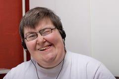 Geestelijk - gehandicapte vrouw met oortelefoon Stock Foto