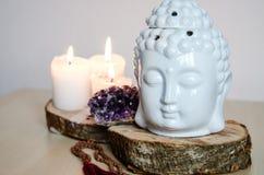 Geestelijk ritueel meditatiegezicht van ametistkaarsen van Boedha op houten witte achtergrond royalty-vrije stock foto's