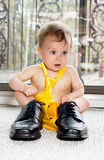 Geeting ready to go to work. Baby boy in adult shoes and a tie Stock Photo