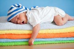Geeuwende slaapbaby op kleurrijke handdoekenstapel Royalty-vrije Stock Foto's