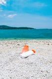 Gefäß mit Sonneschutz auf einem Pebble Beach Lizenzfreies Stockfoto