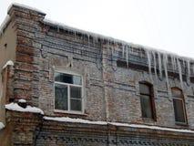 Gefährliche Eiszapfen, die vom Dach von Häusern baumeln lizenzfreies stockbild