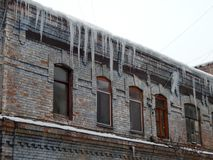 Gefährliche Eiszapfen, die vom Dach von Häusern baumeln lizenzfreies stockfoto