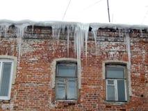 Gefährliche Eiszapfen, die vom Dach von Häusern baumeln stockfotografie
