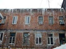 Gefährliche Eiszapfen, die vom Dach von Häusern baumeln stockfotos