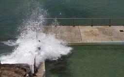Gefährliche Wellen, die über Felsenpool brechen stockfotografie