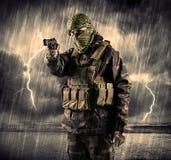 Gefährlicher bewaffneter Terrorist mit Maske und Gewehr in ein Gewitter wi Lizenzfreies Stockbild