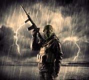 Gefährlicher bewaffneter Terrorist mit Maske und Gewehr in ein Gewitter wi Stockfotografie