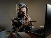 Gefährlicher schauender Hackermann im Hoodie, der Internet-Computersystem seine Augen zeigend warnen über seine Fähigkeit, passw  stockfoto